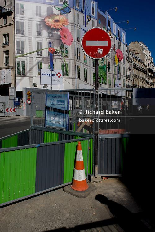 Street roadworks barriers and retail shop hoarding in Rue de Rivoli, Paris.