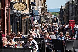 Busy bars and restaurants full of tourists and locals on the Royal Mile in Edinburgh, Scotland, UK