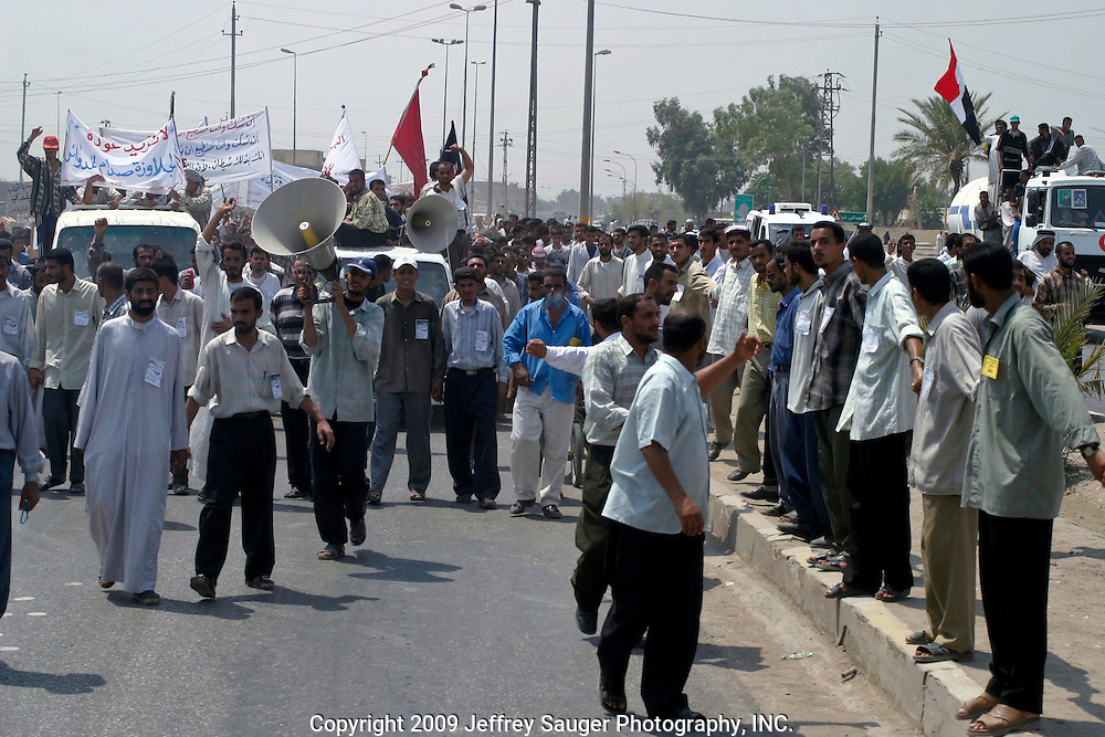 Protestors marching to the City Council Building in Nasiriyah, Iraq, Monday, August 11, 2003. Approximately 3000 peaceful protestors marched on the building, where Coalition Provencial Authority instilled city council members were holed up, demanding they resign and the citizens have the right to elect their own leaders. Heavily armed Italian troops guarded the buiding as Italian helicopters flew overhead. After several hours of negotiations, the protestors said they would not leave until the resignations were complete. Apparently by the end of the day, the resignations finally came.