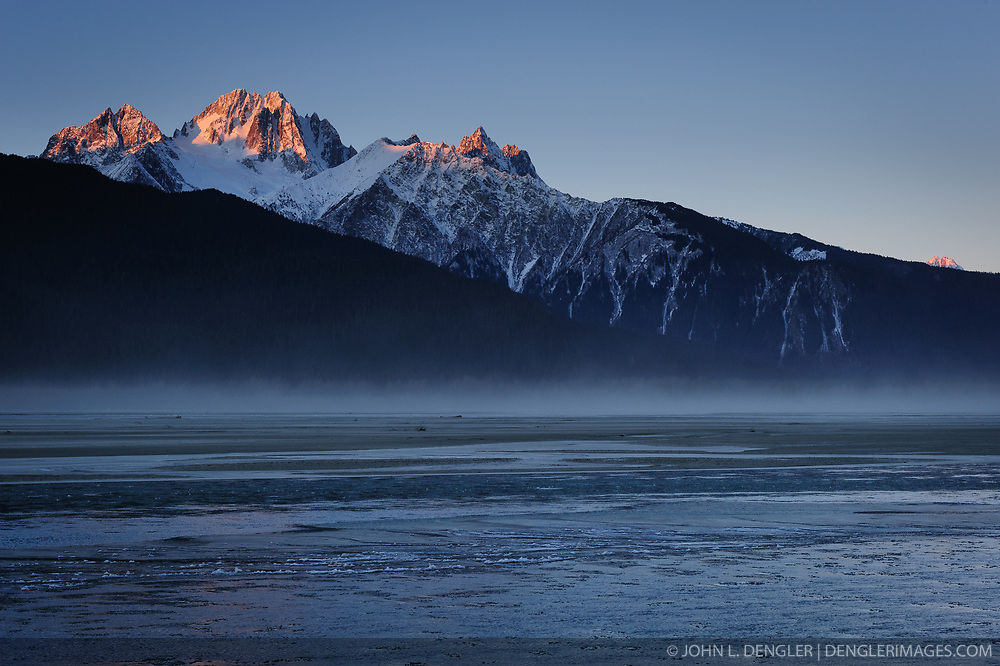 Early morning sunlight reaches the top peaks of Mt. Emmerich as fog-like blowing dust from the silt of banks the Chilkat River blows down the river. During late fall, bald eagles congregate along the Chilkat River to feed on salmon. This gathering of bald eagles in the Alaska Chilkat Bald Eagle Preserve is believed to be one of the largest gatherings of bald eagles in the world.