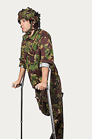 Young soldier holding crutches against gray background