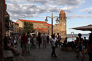 Atmospheric view of people strolling on the Boulevard du Boramar with the Eglise Notre Dame des Anges in the background, Collioure, France. The bell tower was converted from a medieval lighthouse and the Mediterranean Gothic style nave was built in 1684. The dome was added to the bell tower in 1810. Picture by Manuel Cohen.
