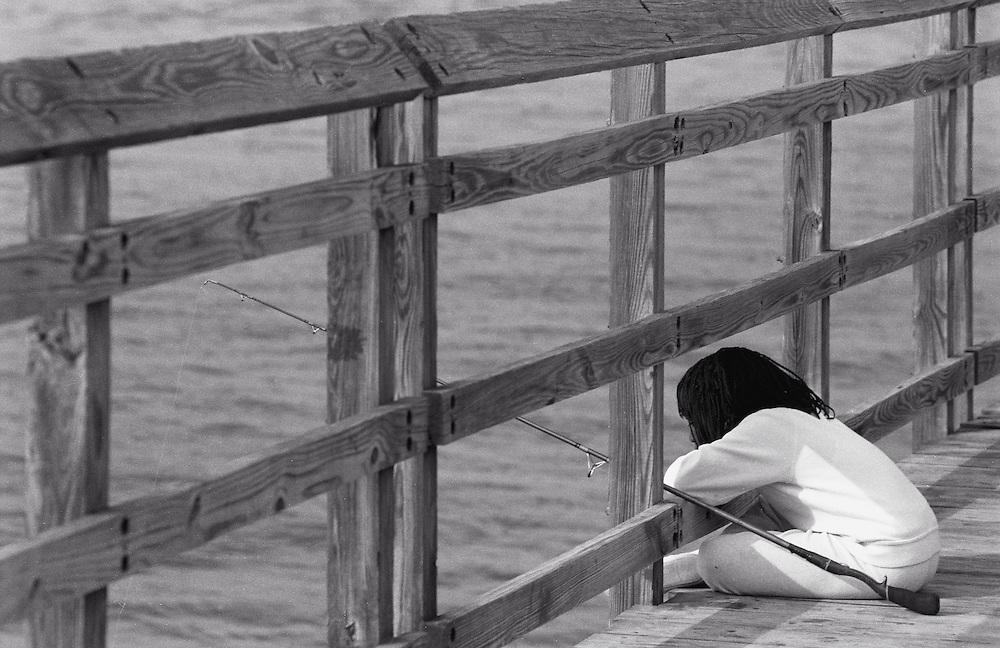Child fishing on pier