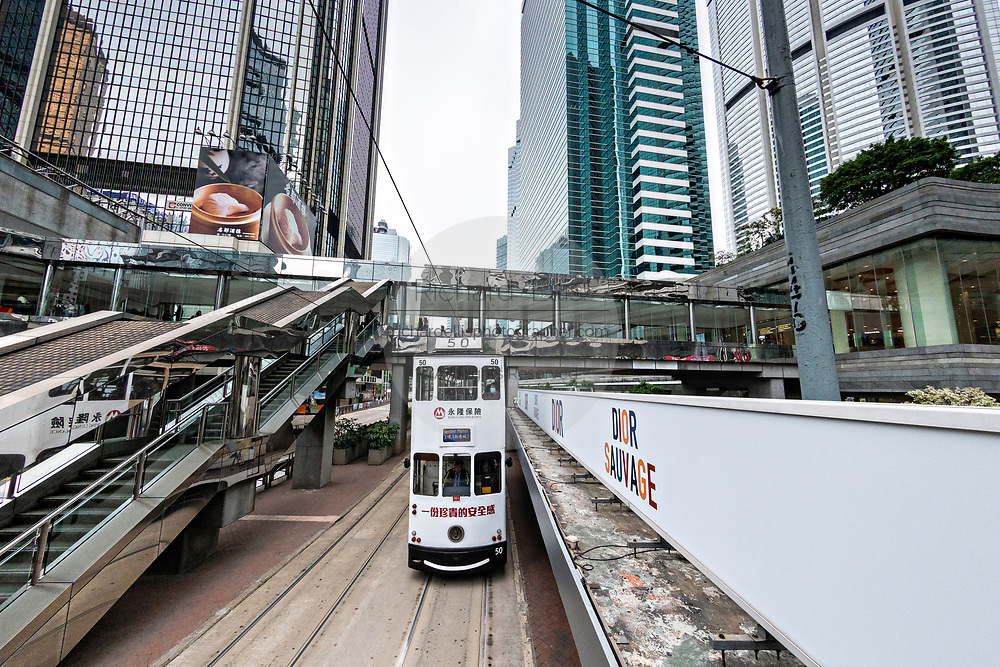 A historic double decker tram passes the Admiralty Center in the central district of Hong Kong.