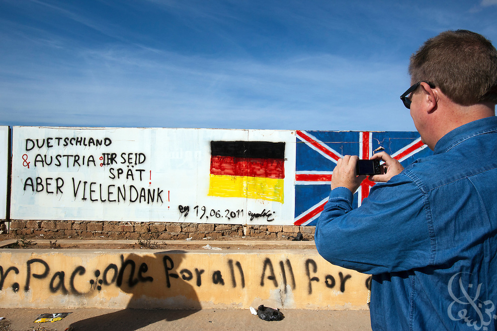 Dr. Ronald Meinardus, Regional Director of the Friedrich Naumann Foundation for Liberty (FNF) takes a photo of a graffiti message addressed to Germany on a street in Benghazi, Libya December 18, 2011.  (Photo by Scott Nelson, for Der Spiegel)