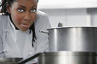Female chef near saucepan in kitchen portrait