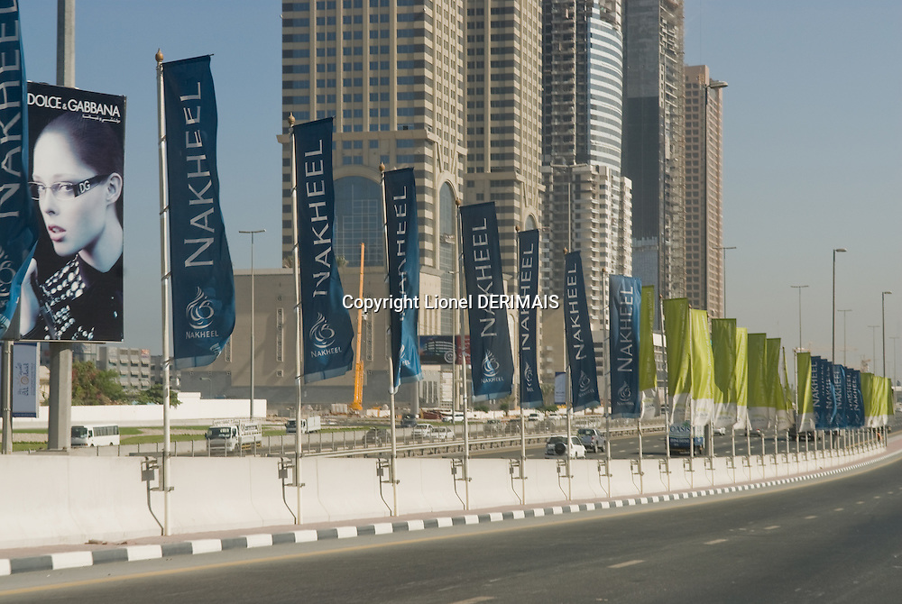 Nakheel flags flutter in the Persian gulf wind along a Dubai highway. Dubai, one of the seven emirates and the most populous of the United Arab Emirates sits on the southern coast of the Persian gulf.