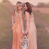Two young women standing together in the nature wearing pastel colored dresses and holding a white birdcage