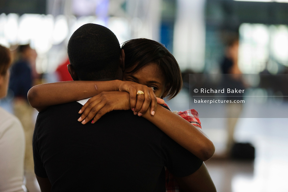 "A departing lover hugs her boyfriend farewell before her long-haul flight in the Departures concourse at. Heathrow Airport's Terminal 5. While embracing her young man, she gazes off into the distance amid the otherwise busy airport terminal where the emotions of parting as well as the joys of reunited loved-ones are played out in various parts of aviation hubs around the world. They are both in their own worlds, removed from the noise and confusion of other passengers. Her departure is brief and yet their sadness of being separated is plainly too much to bear. From writer Alain de Botton's book project ""A Week at the Airport: A Heathrow Diary"" (2009). ."