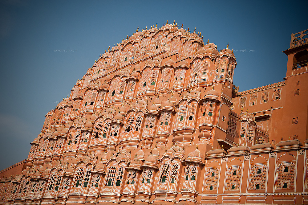 "Hawa Mahal ot the ""Palace of Winds"", is a palace in Jaipur, India. It was built in 1799 by Maharaja Sawai Pratap Singh, and designed by Lal Chand Usta  in the form of the crown of Krishna, the Hindu  god. Its unique five-story exterior is also akin to the honeycomb of the beehive with its 953 small windows called jharokhas  that are decorated with intricate lattice work. The original intention of the lattice was to allow royal ladies to observe everyday life in the street below without being seen, since they had to observe strict ""purdah"" (face cover)."