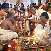 The bride and groom, and the close family during the wedding ceremony while the priest keeps the sacred fire going.