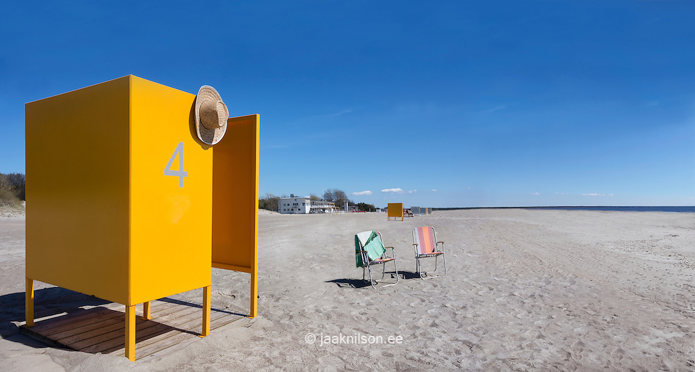 Yellow dressing cabin number 4 on empty sandy Pärnu beach in Estonia. Off season, dressing room and two beach chairs.