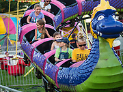 "26 JUNE 2019 - CENTRAL CITY, IOWA: Teenagers ride the ""Dragon Wagon"" on the midway at the Linn County Fair. Summer is county fair season in Iowa. Most of Iowa's 99 counties host their county fairs before the Iowa State Fair, August 8-18 this year. The Linn County Fair runs June 26 - 30. The first county fair in Linn County was in 1855. The fair provides opportunities for 4-H members, FFA members and the youth of Linn County to showcase their accomplishments and talents and provide activities, entertainment and learning opportunities to the diverse citizens of Linn County and guests.    PHOTO BY JACK KURTZ"