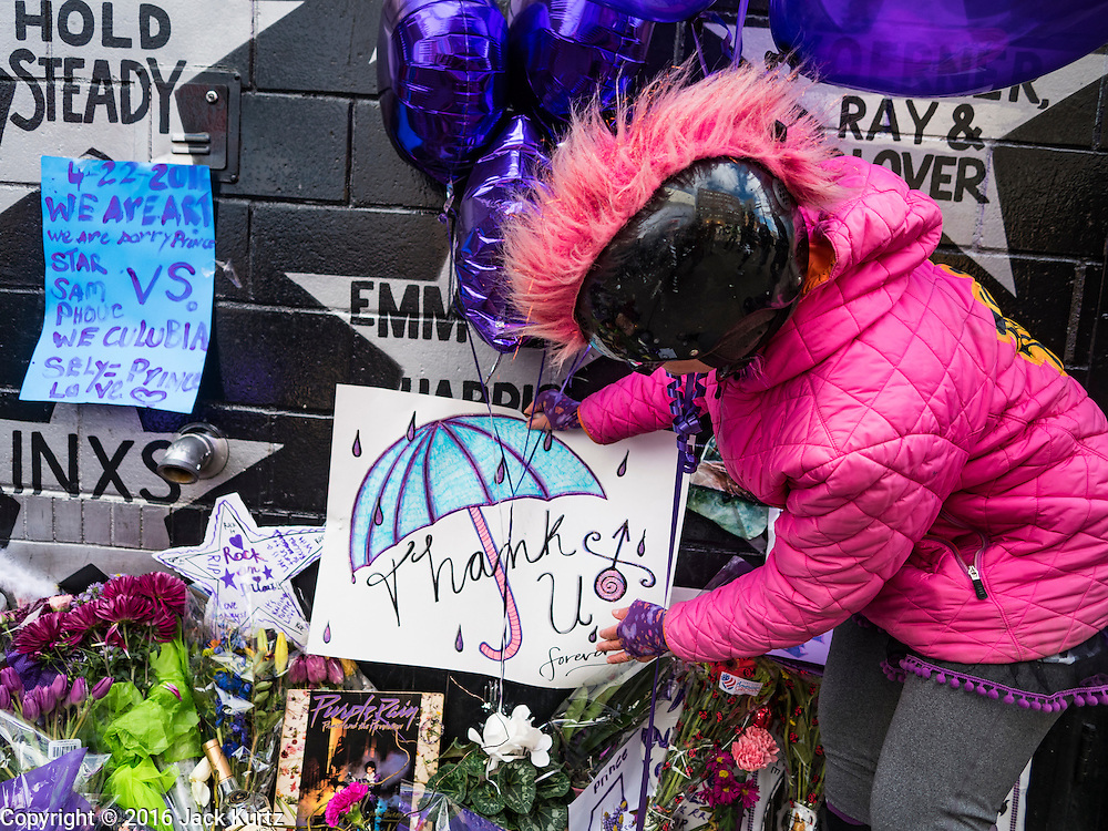 """22 APRIL 2016 - MINNEAPOLIS, MN: MINA LEIERWOOD, from Minneapolis, MN, leaves a thank you card at a memorial for Prince in front of 1st Ave in Minneapolis. She said listened to Prince's music all through high school. Thousands of people came to 1st Ave in Minneapolis Friday to mourn the death of Prince, whose full name is Prince Rogers Nelson. 1st Ave is the nightclub the musical icon made famous in his semi autobiographical movie """"Purple Rain."""" Prince, 57 years old, died Thursday, April 21, 2016, at Paisley Park, his home, office and recording complex in Chanhassen, MN.    PHOTO BY JACK KURTZ"""