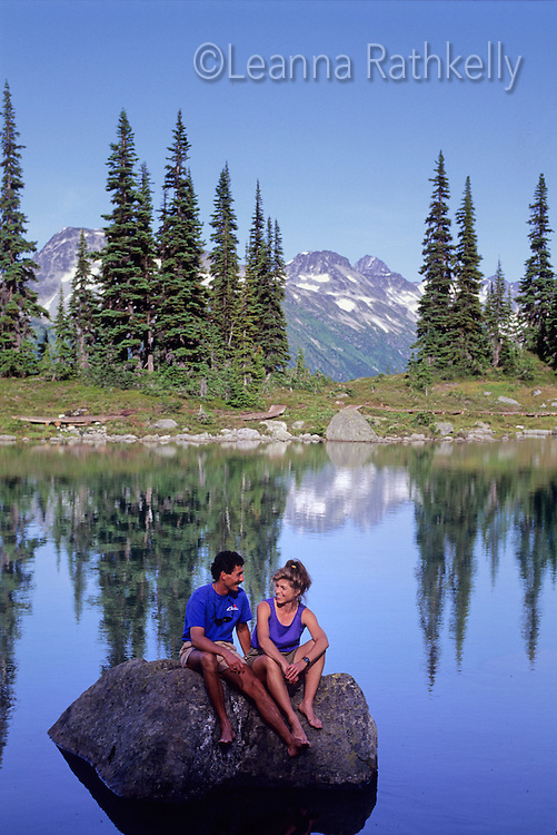 A couple relaxes by Harmony Lake, Whistler mountain summer evening.