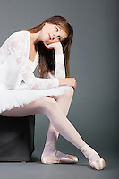 Thoughtful young ballet dancer sitting over grey background