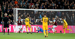 West Ham United goalkeeper Joe Hart (centre) dives but cannot save Brighton & Hove Albion's Glenn Murray (right) scoring his team's opening goal