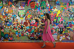"© Licensed to London News Pictures. 04/10/2018. LONDON, UK. A staff member walks next to ""Speculative Entertainment No 1, London Edition"" by Uji Hahan Handoko Eko Saputro. Preview of Moniker Art Fair, taking place during Frieze Week at the Old Truman Brewery, near Brick Lane.  Now in its tenth year, the fair embraces contemporary urban art from emerging and established artists  This year, the show's theme is 'Uncensored', shedding light on social, economic and ecological issues, and is open 4 to 7 October.  Photo credit: Stephen Chung/LNP"