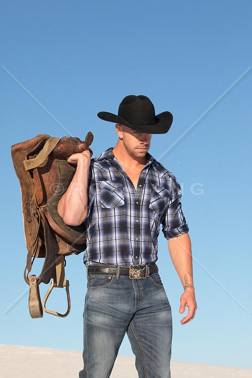 cowboy holding a saddle
