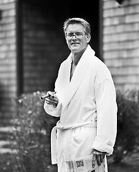 Mature man outside in a white bathrobe holding a cigar and newspaper