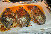 Grilled fish on an oven tray. The tray is covered in aluminium foil and baking paper to prevent contact with the not so healthy aluminium