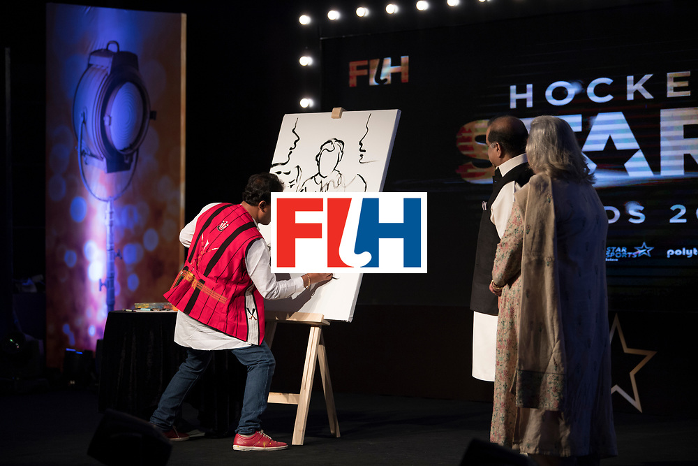 CHANDIGARH, INDIA - FEBRUARY 23: Speed Painter Rabin Bar of Assam sketches a painting of the signatures of Dr. Narinder Dhruv Batra, President of The International Hockey Federation and his wife Mrs Chetna Batra during the FIH Hockey Stars Awards 2016 at Lalit Hotel on February 23, 2017 in Chandigarh, India. (Photo by Ali Bharmal/Getty Images for FIH)