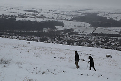© Licensed to London News Pictures.04/03/16. Ilkley, UK. Two walkers make their way up onto the snow covered moors in Ilkley, West Yorkshire. Forecasters are predicting more cold weather this week as Storm Jake takes hold. Photo credit : Ian Hinchliffe/LNP