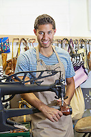 Portrait of handsome young shoemaker working on machinery