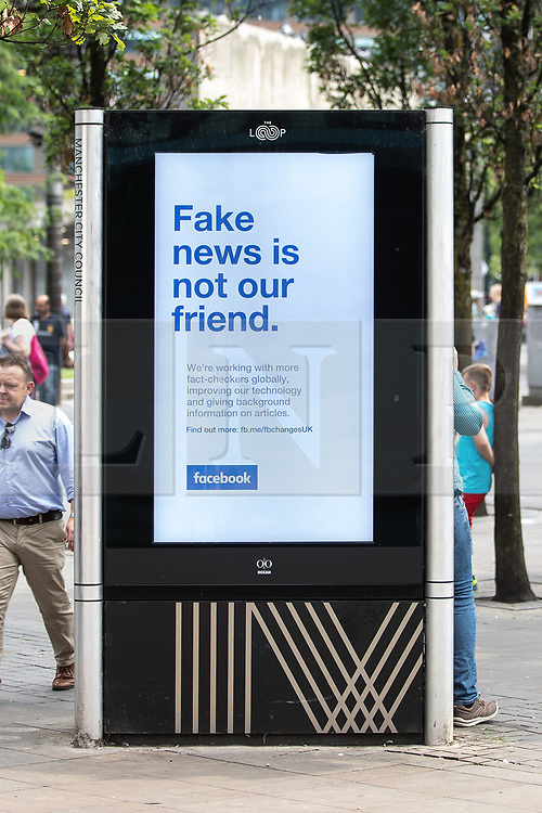 """© Licensed to London News Pictures . 26/07/2018. Manchester , UK . An advert for social media platform Facebook in Piccadilly Gardens in Manchester City Centre , which reads """" Fake news is not our friend"""" . Photo credit : Joel Goodman/LNP"""
