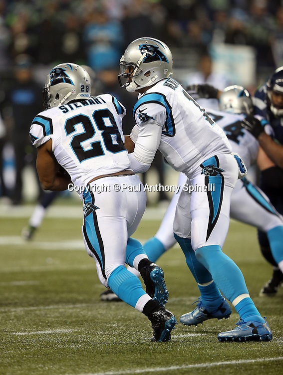 Carolina Panthers quarterback Cam Newton (1) fakes a handoff to Carolina Panthers running back Jonathan Stewart (28) and throws a third quarter completed pass during the NFL week 19 NFC Divisional Playoff football game against the Seattle Seahawks on Saturday, Jan. 10, 2015 in Seattle. The Seahawks won the game 31-17. ©Paul Anthony Spinelli