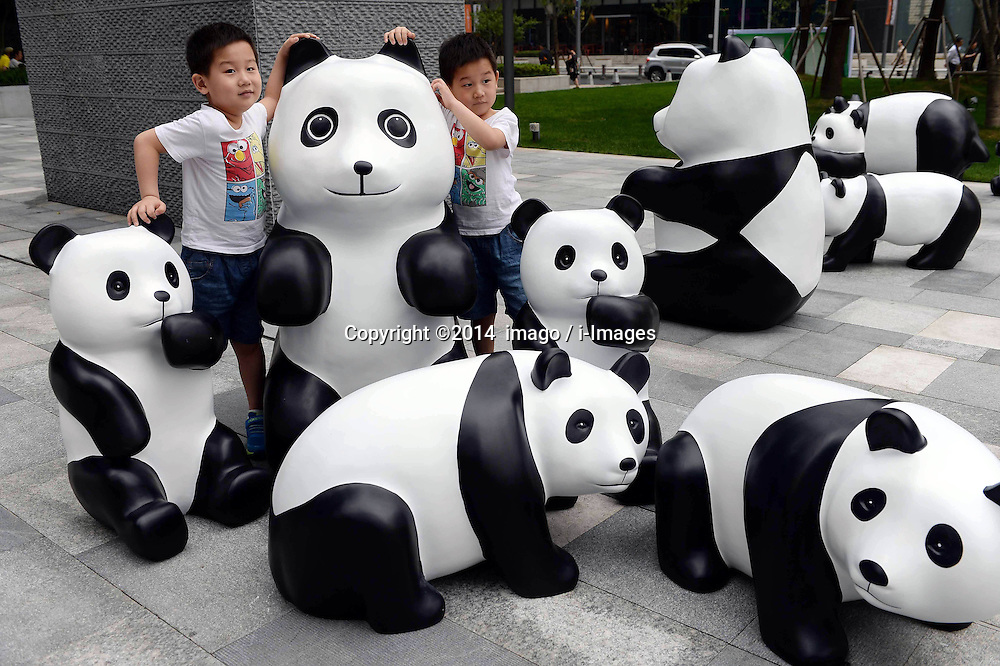 61633275<br /> Children pose for photos with lovely pandas during the 1St panda exhibition at Kerry Centre Square in Shanghai, East China, June 2, 2014. A total of 100 pandas made of leftover moso bamboos were displayed during the exhibition, Monday, 2nd June 2014. Picture by  imago / i-Images<br /> UK ONLY