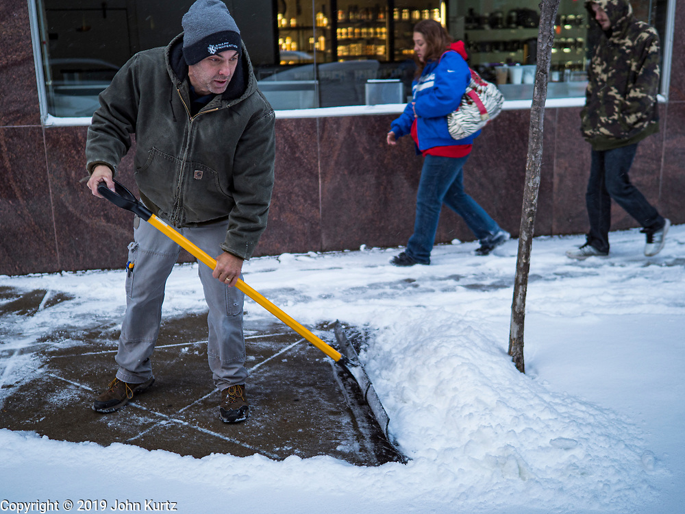 11 NOVEMBERS 2019 - DES MOINES, IOWA: A man shovels snow on a sidewalk in downtown Des Moines while pedestrians walk past him. About three inches of snow fell in the Des Moines area Sunday night into Monday morning snarling the Monday morning rush hour and delaying central Iowa schools by about two hours.       PHOTO BY JACK KURTZ