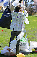 April 21, 2013 - Roslyn Harbor, New York, U.S. - At Celebrate Earth Day at Nassau County Museum of Art, JOHN CLOUD KAISER, an artist from NYC art collective Free Style Arts Association, works on the Bag Flag made of recycled plastic shopping bags, while wearing his white jacket colorfully decorated by visitors.
