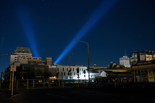The White Lights of Hope shine out behind the Hotel Grand Chancellor from the dark CBD. & Light Beam Memorial switched on one year after the Christchurch ...