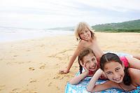 Children reclining hand on cheek on beach towel on sandy Beach