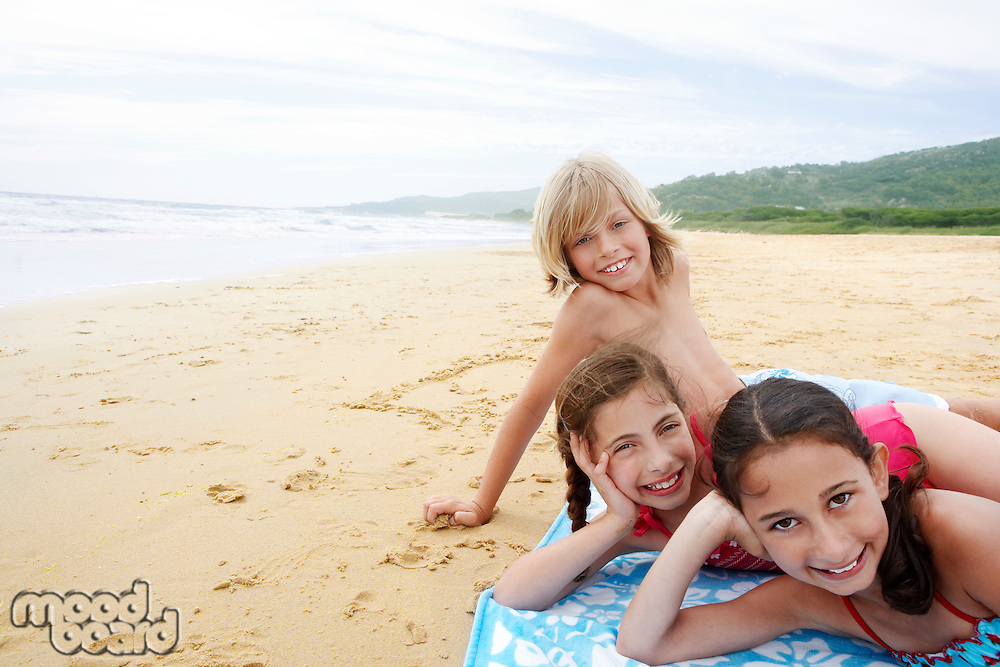 Children reclining hand on cheek on beach towel on sandy Beach
