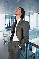 Businessman standing in office corridor looking up