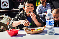 The Naga Chili Eating Competition at the Hornbill Festival in Nagaland, India. The Naga chili is called the hottest chili in the world. Contestants here have 20 seconds to eat as many chilis as possible. They are allowed to chew even after their 20 seconds are up, but if they spit out any chili, they are disqualified. Here, last year's runner-up makes a go for the crown by taking down 14 chilis. Like many of the other local contestants, his strategy involved cramming as many chilis into his mouth as possible during the 20-scond time limit. Unfortunately, he probably thought as he rode in the ambulance to the hospital later, he fit in the most.