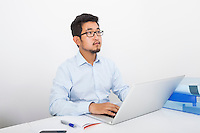 Thoughtful businessman with laptop sitting at desk in office