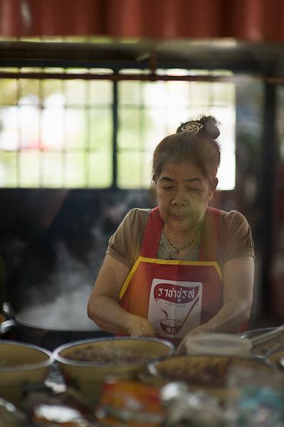 A woman, preparing food in her street kitchen