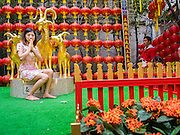 "19 FEBRUARY 2015 - BANGKOK, THAILAND: A woman is photographed next to a statue of a goat on Chinese New Year at Wat Mangkon Kamalawat in Bangkok. 2015 is the Year of Goat in the Chinese zodiac. The Goat is the eighth sign in Chinese astrology and ""8"" is considered to be a lucky number. It symbolizes wisdom, fortune and prosperity. Ethnic Chinese make up nearly 15% of the Thai population. Chinese New Year (also called Tet or Lunar New Year) is widely celebrated in Thailand, especially in urban areas that have large Chinese populations.    PHOTO BY JACK KURTZ"