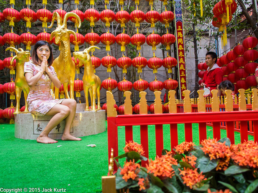 """19 FEBRUARY 2015 - BANGKOK, THAILAND: A woman is photographed next to a statue of a goat on Chinese New Year at Wat Mangkon Kamalawat in Bangkok. 2015 is the Year of Goat in the Chinese zodiac. The Goat is the eighth sign in Chinese astrology and """"8"""" is considered to be a lucky number. It symbolizes wisdom, fortune and prosperity. Ethnic Chinese make up nearly 15% of the Thai population. Chinese New Year (also called Tet or Lunar New Year) is widely celebrated in Thailand, especially in urban areas that have large Chinese populations.    PHOTO BY JACK KURTZ"""