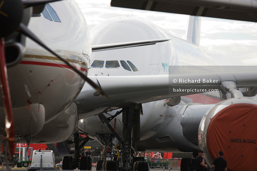 Security staff and static display aircraft lined-up at the Farnborough Airshow, the A380 at the back and a 777 in front.