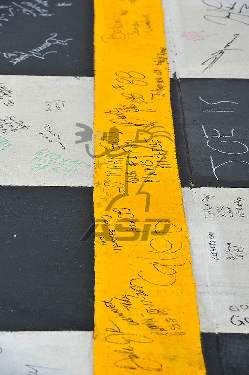 Brooklyn, MI - JUN 17, 2012: Fans write messages on the start finish line during before race action for the Quicken Loans 400 race at the Michigan International Speedway in Brooklyn, MI.