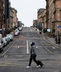 Glasgow, Scotland, UK. 26 March, 2020. Views from city centre in Glasgow on Thursday during the third day of the Government sanctioned Covid-19 lockdown. The city is largely deserted. Only food and convenience stores open. Pictured; Masked man crosses street in central Glasgow. Iain Masterton/Alamy Live News