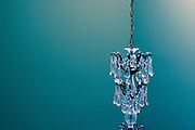 Hanging crystal chandelier with turquoise wall in background.