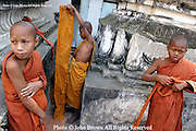 Young Khmer novice Buddhist monks put on their orange robes at a temple in Phnom Penh, Cambodia.