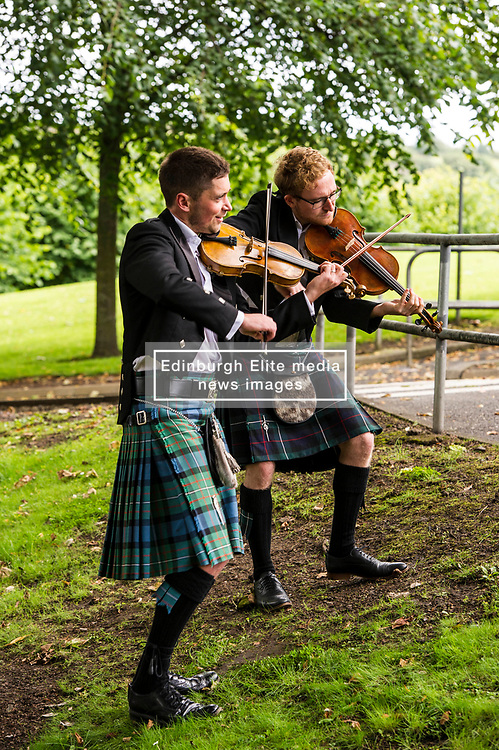 Pictured: Thoren Ferguson and Lewis Kelly (glasses) play the Owen and Sasson violins respectively<br /> Violinists were on hand to play at the first public appearance of two instruments made in honour of war poets,  Wilfred Owen and Siegrfried Sassoons.  The violins, crafted by Steve Burnett and insured for £25,000 each, were played at the sycamore tree from which they were made at the Craiglockhart Campus of Napier University in Edinburgh. <br /> Ger Harley | EEm 7 August  2017