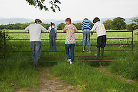 Parents with three children (5-9) standing on fence in countryside
