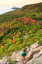 "A young couple hiking ""The Beehive"" in fall in Maine's Acadia National Park."